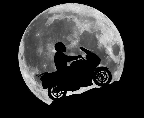 A motorcycle silhouetted against the moon