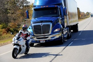 A motorycle being followed by a large truck