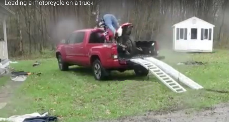 Man trying to ride a motorcycle into the back of a truck.