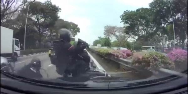 Officers of Singapore's Rapid Deplpyment Troops crash on a motorcycle